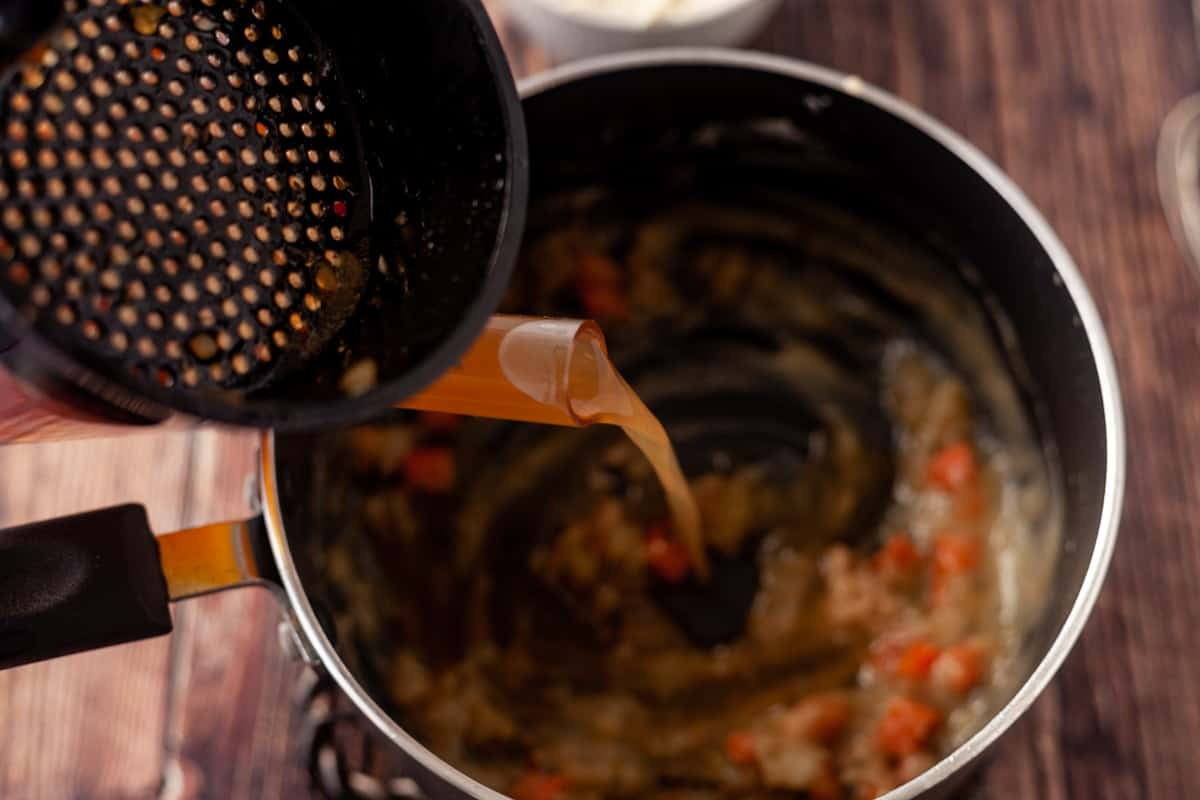 pouring stock in a saucepan with roux