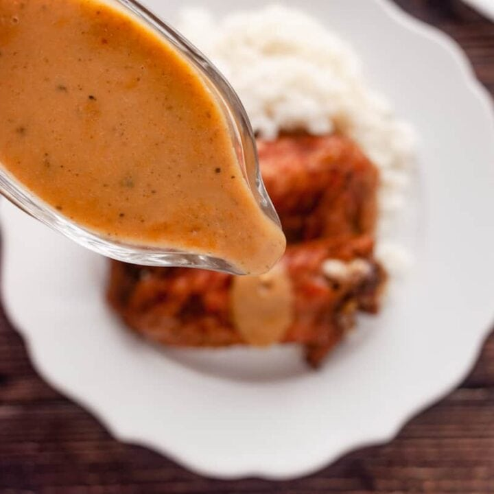 pouring sage butter turkey gravy over baked turkey wings