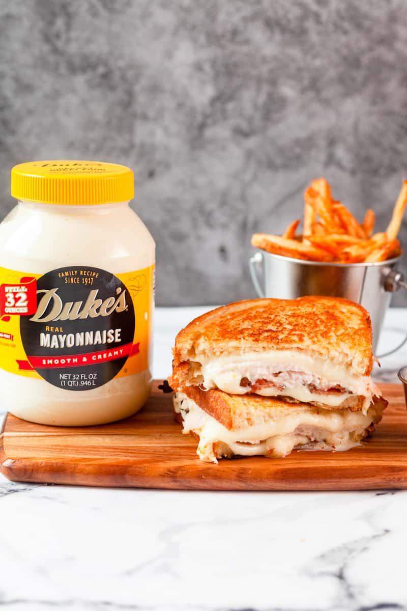 turkey grilled cheese cut and stacked next to a jar of duke's mayo
