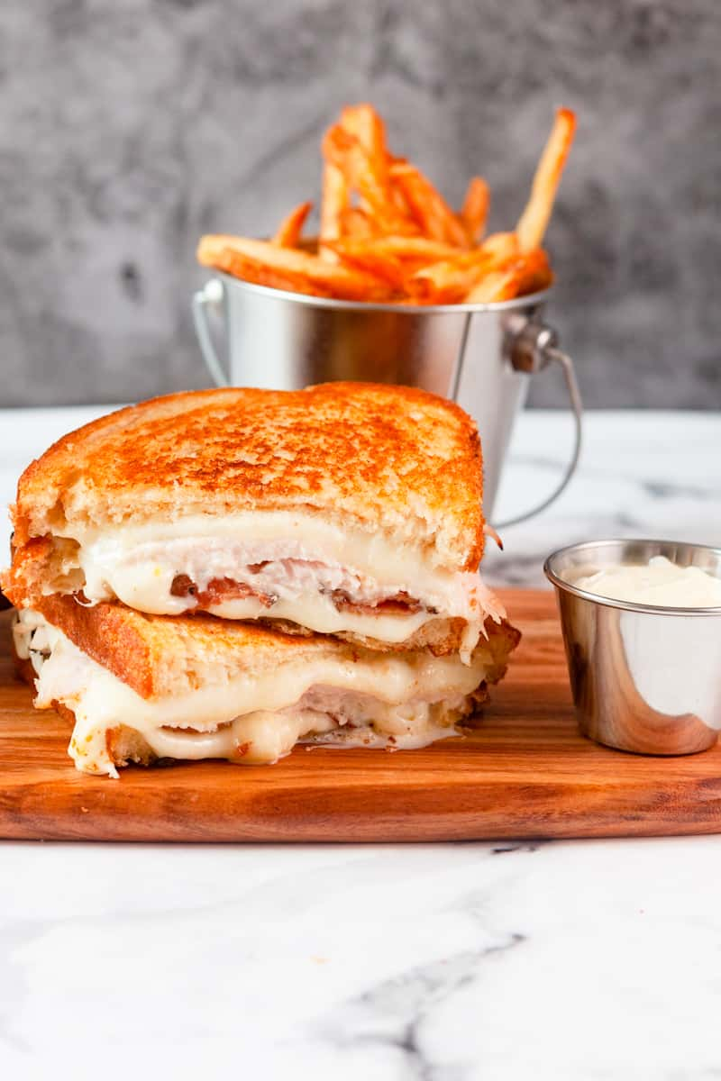 turkey grilled cheese cut and stacked on a cutting board in front of crispy french fries
