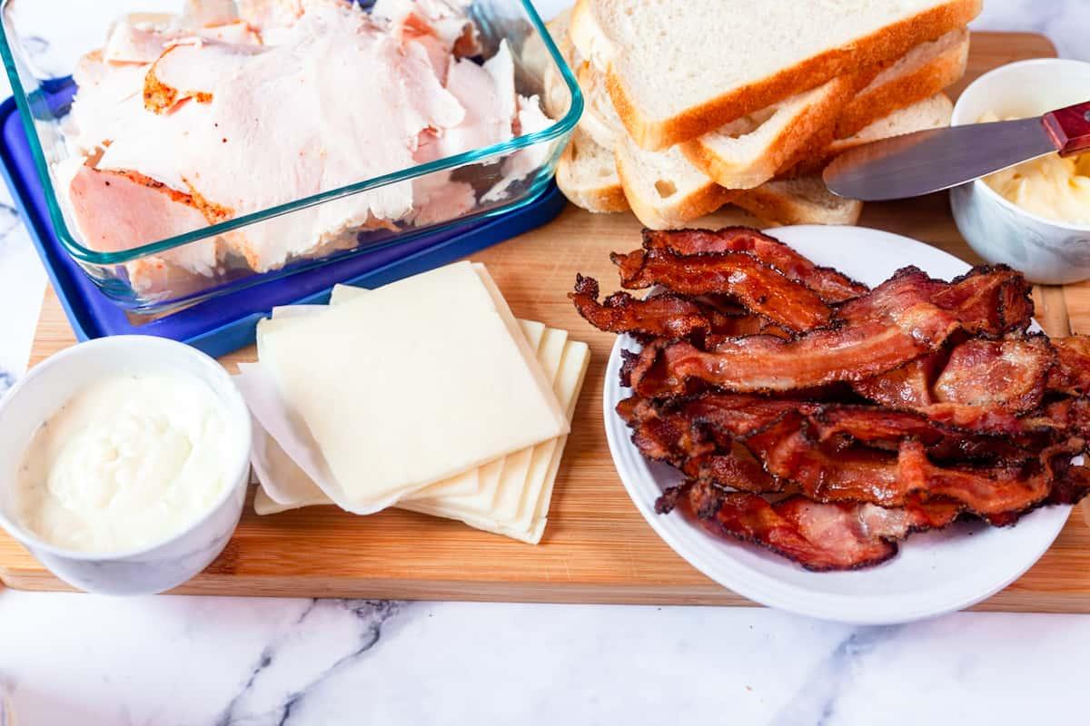 turkey, cheese, nad bacon on a cutting board