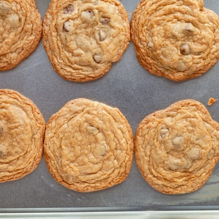 crinkled brown butter chocolate chip cookies on a sheet pan