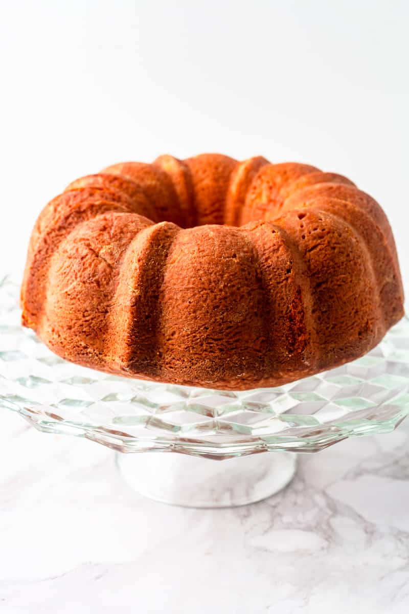 a whole cream cheese pound cake on a glass cake stand