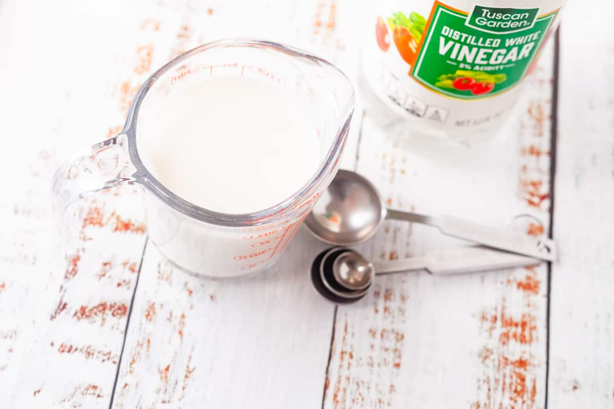 cup of milk next to a bottle of white vinegar