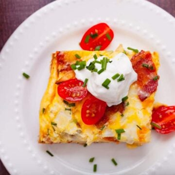 a slice of french fry casserole on a white plate topped with sour cream and tomatoes