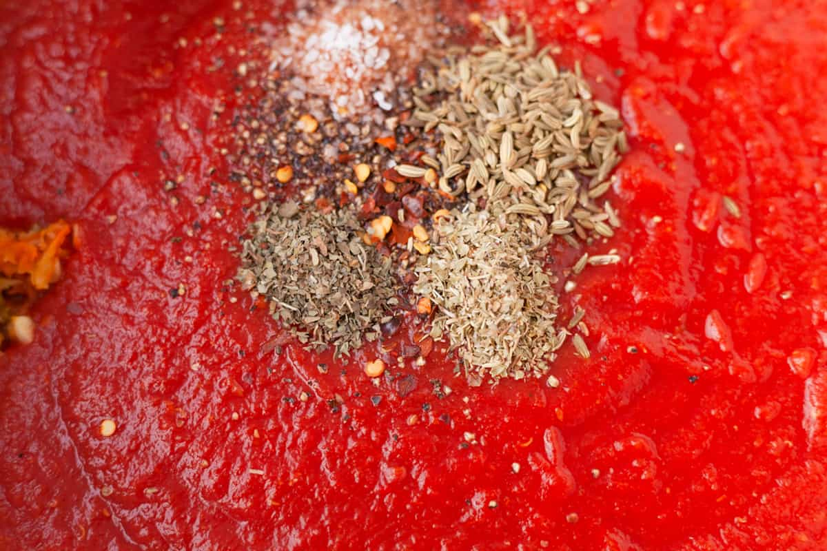 dried spices on top of marinara sauce
