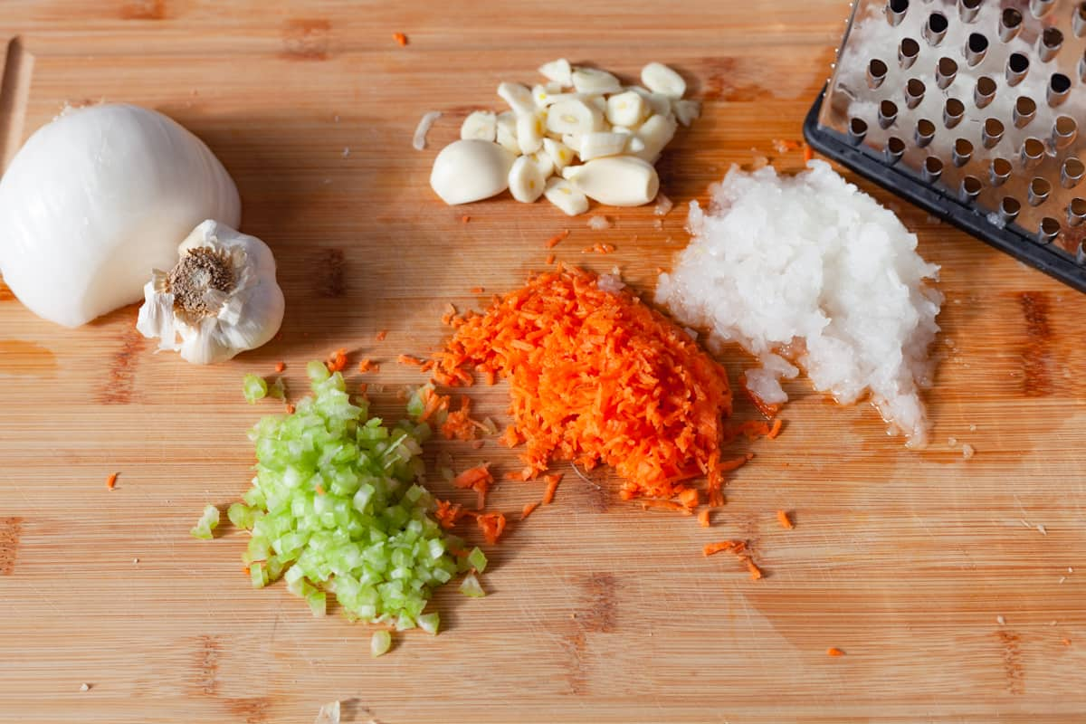 grated celery, onion, carrot, and garlic on a cutting board