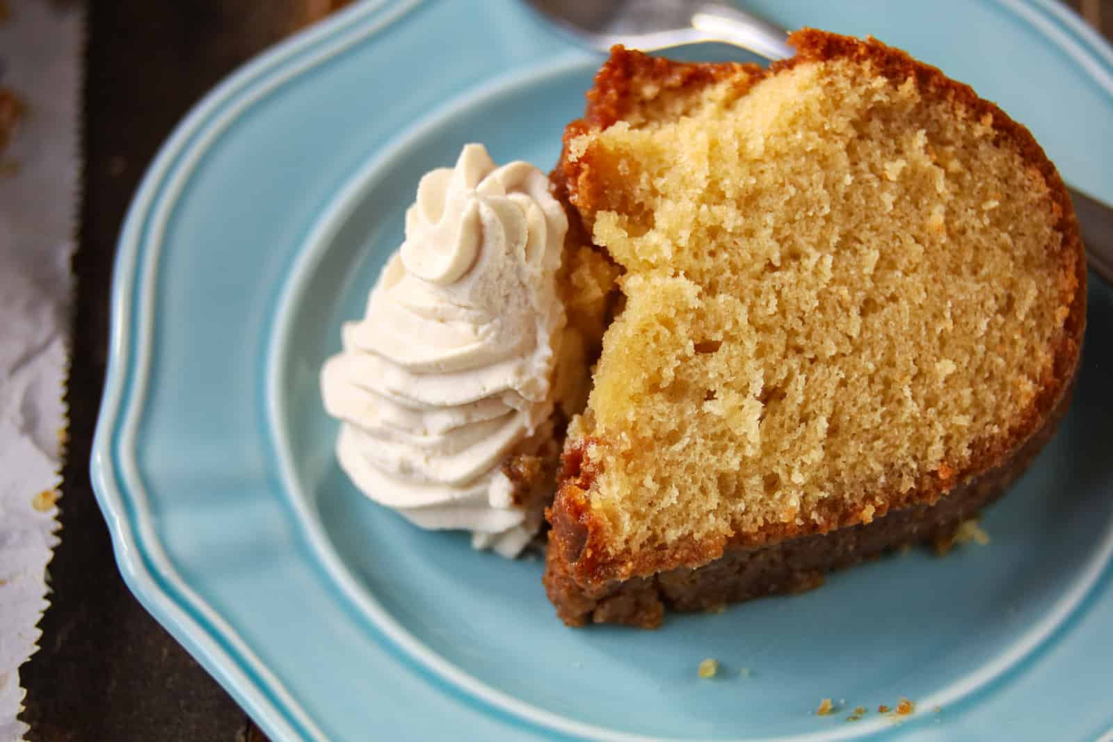 slice of brown sugar pound cake on a plate with whipped cream